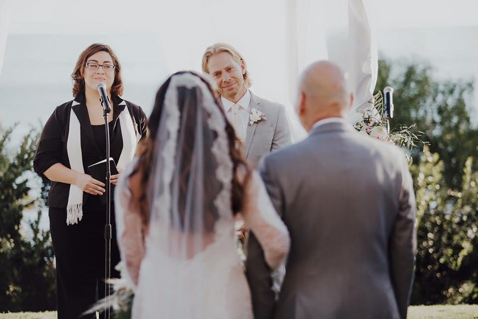 Groom smiles bride walking down aisle